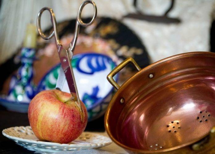 manzana con tijeras clavadas